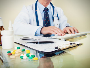 Doctor on his workplace with computer, pills, tablets, write a p