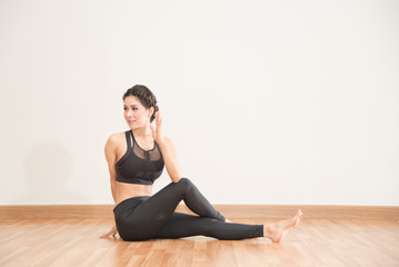 young woman practicing yoga on wooden floor