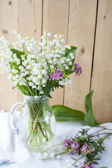 White lily of the valley on a light wooden table