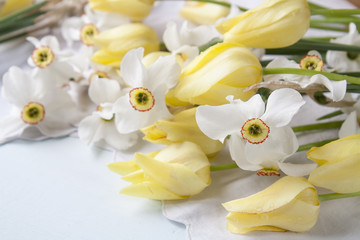 White daffodils narcissus and yellow tulips on a light wooden table. Beautiful spring floral background.