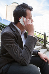 Businessman resting from work and while sending messages and talking with his smartphone. He is sitting on the stairs.