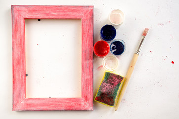 Painted wood picture frame with paints, sponge and paintbrush