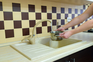 A girl collects water in a saucepan in a modern kitchen