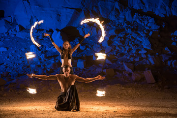Fireshow performance in the desert near the rock illuminated with blue. Motions are blurred Wall mural