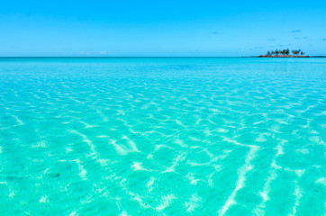 Turquoise, crystal clear water and a small island in the background on Eleuthera (Bahamas).
