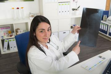 Junge Ärztin sieht sich ein Röntgenbild in der Arztpraixs  an