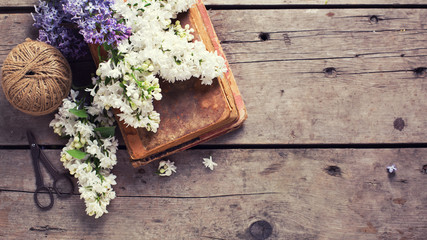 Background with fresh aromatic lilac flowers  on old books on vi