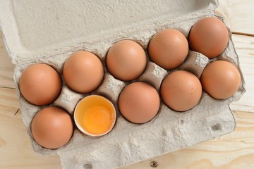 brown eggs in carton with broken egg