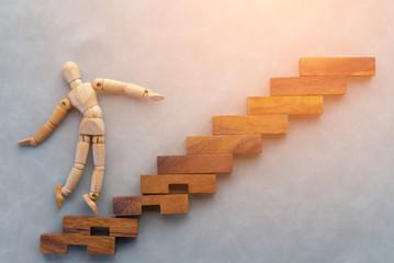 wooden figure walking up wooden stair business concept.jpg