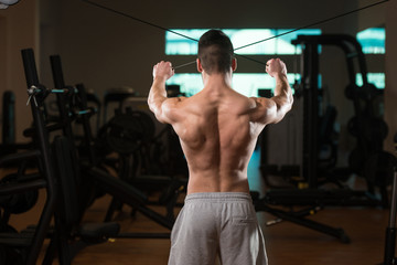 Bodybuilder Exercising Back On Cable Machine