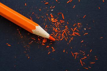orange pencil shavings on black