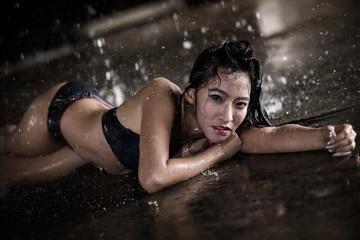Sexy bikini girl among the rain and water
