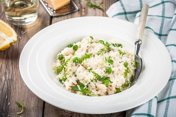Homemade risotto with chicken, green peas, arugula and parmesan