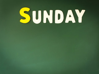 Wooden Sunday on Green Board. Wood Sunday word on blackboard with copy space. Weekend.