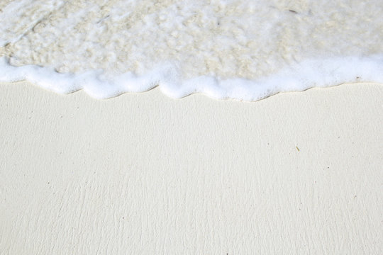 Close-up of white coastline beach with waves