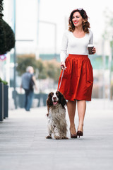 Young woman walking her dog and drinking coffee to go