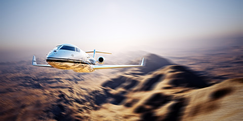 Photo of silver modern and luxury generic design private jet flying in blue sky at sunrise.Uninhabited desert mountains background.Business travel picture.Horizontal,motion blurred effect.3d rendering
