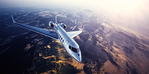 Realistic photo of silver generic design private Jet flying over the mountains. Empty blue sky with sun at background.Business Travel by modern Luxury Plane.Horizontal.Closeup photo. 3d rendering