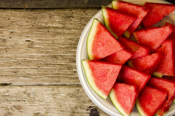 Seedless watermelon cut into wedges on wood background