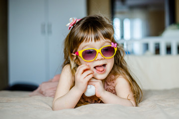 fashion little girl in glasses lying on her belly and smiling