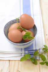brown eggs in a bowl with mint leaf on a napkin closeup
