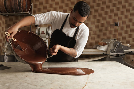 Black man professional chief pours tasty melted chocolate from one big steel pot to vintage marble table in his artisan rustic kitchen with industrial retro machines. Mirrored in chocolate on table.