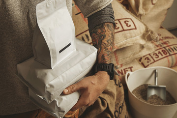 Tattooed barista holds package bags with freshly baked coffee beans ready for sale and delivery Plastic basket near big bags europalet in warehouse behind Professional alternative roasting and brewing