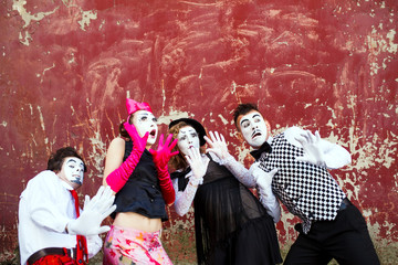 Four mimes standing in awe at the background of a red wall.