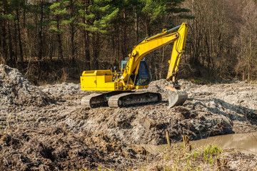 large yellow excavator in dirt on a construction site against bl