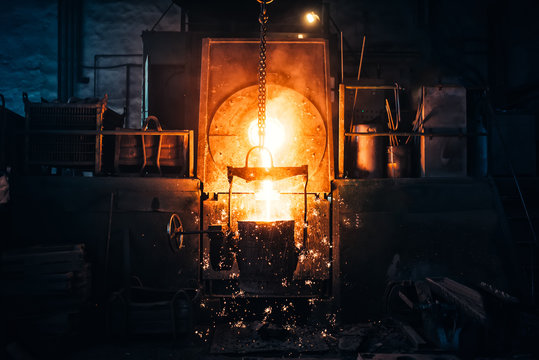 Smelting metal in a metallurgical plant. Liquid iron from metal ladle pouring in castings at factory