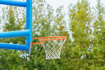 basketball backboard with a ring on a street court