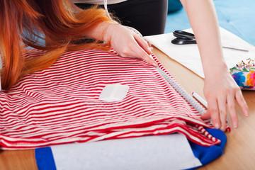 Woman measuring pattern on fabric.