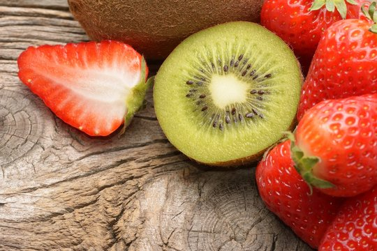 Kiwi and strawberry on wooden background