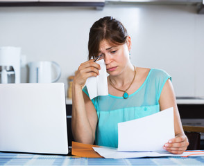 Unhappy housewife reading banking statement