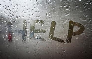 "The ""Help"" inscription on the sweaty glass"