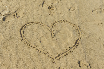 Heart drawn in the sand of the beach. Love concept.