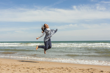 Full shot of a smily teenager jumping in the seashore of the bea