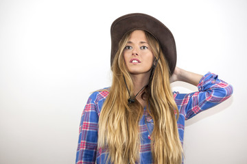 Portrait of beautiful blonde woman with plaid shirt and a cowboy