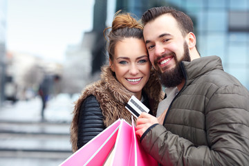 Young couple shopping in the city with credit card