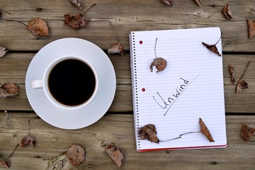 relaxation and writing concept. A notebook and coffee outside on a deck with leaves.