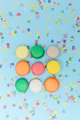 Macaroons selected focus toned, colorfull cakes on confetti back