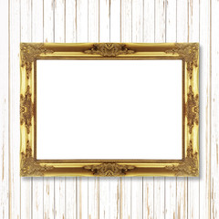 Antique gold frame on white wooden wall ;. Empty picture frame o