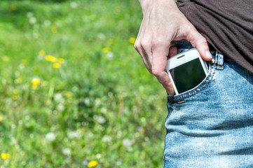 Woman holding smartphone in the jeans pocket at the park