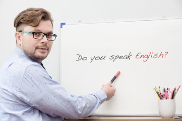 Young caucasian teacher pointing on title Do you speak english
