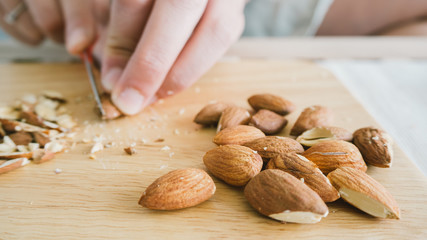 Woman is chopping almonds.