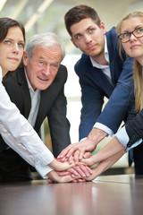 Geschäftsleute stapeln Hände im Büro