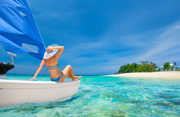 Woman traveler sit at the stern of sailboat looking to the beach