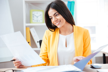 Smiling businesswoman working with papers