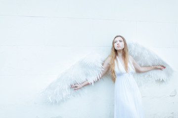 Portrait of sad angel girl with the big white wings. She stands near the white wall