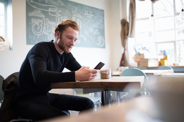 Young Man Checking Mobile Phone In Coffee Shop